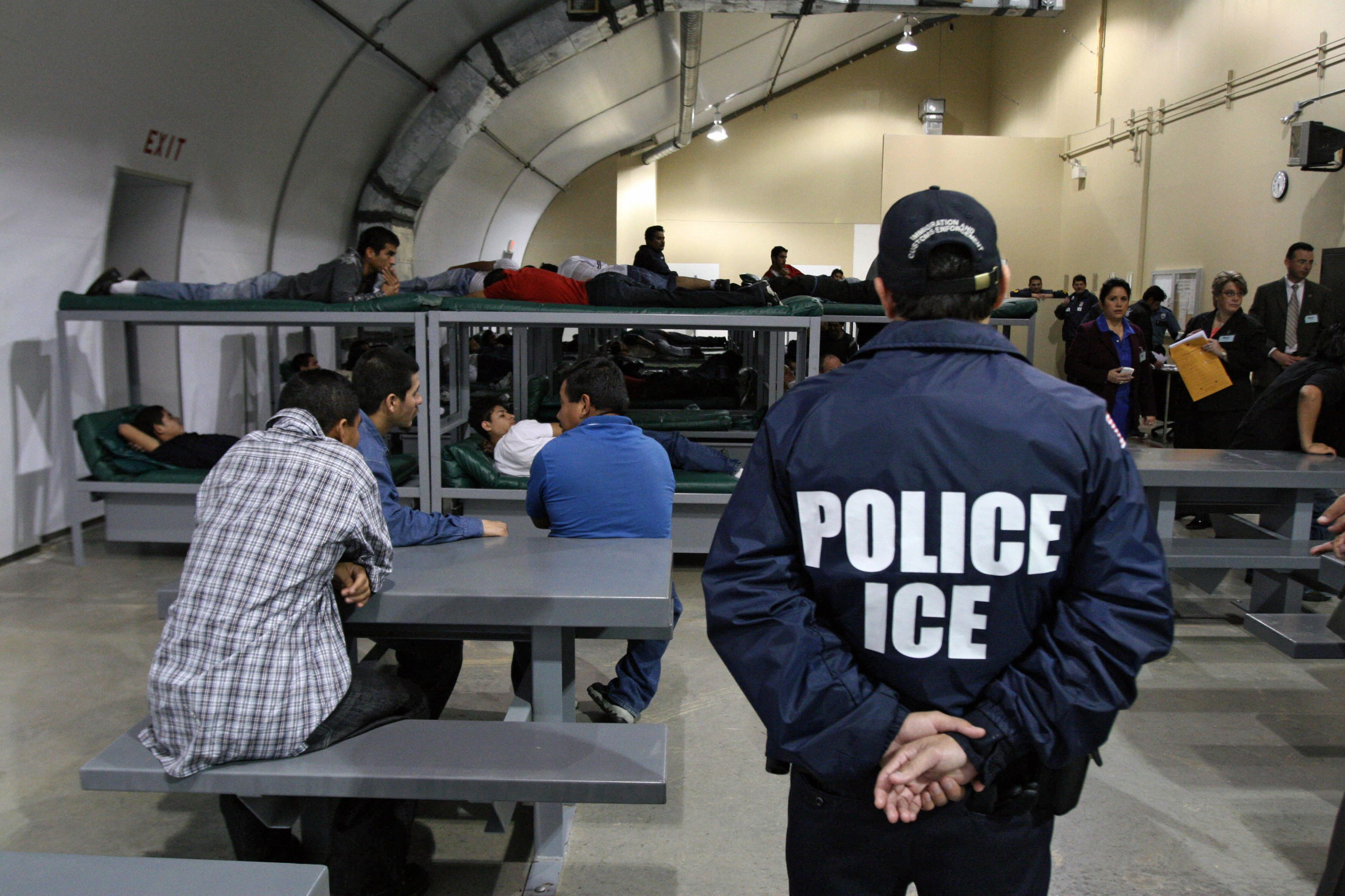 TO GO WITH AFP STORY BY CARLOS MARIO MARQUEZ An Immigration and Customs Enforcement (ICE) officer guards a group of 116 Salvadorean immigrants that wait to be deported,at Willacy Detention facility in Raymondville, Texas on December 18, 2008 early morning. The Willacy facility is used by the US Immigration and Customs Enforcement agency (ICE) to keep illegal immigrants in detention before they are deported. Today, 116 Salvadorean nationals --83 men and 33 women-- were woken up at 4 a.m. and transported in buses under strict surveillance to Harlengen's airport to be taken back to El Salvador.  AFP PHOTO/ Jose CABEZAS (Photo credit should read Jose CABEZAS/AFP/Getty Images)