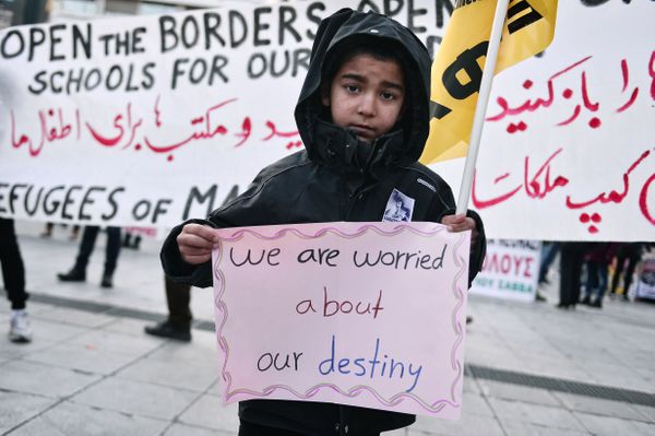 A boy carries a sign as migrants and refugees demonstrate in Athens on January 21, 2017.