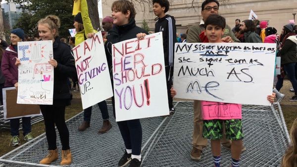 Children hold banners as they stand beside their parents in Washington D.C.
