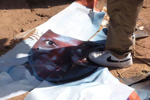 A man walks on a ripped electoral poster of Gambia's outgoing president Yahya Jammeh, in a street of...