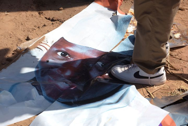 A man walks on a ripped electoral poster of Gambia's outgoing president Yahya Jammeh, in a street of Bijilo, on December 4, 2