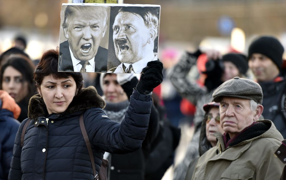 A participant of a Women's March in Helsinki holds up a poster depicting US President Donald Trump and German dictator Adolf