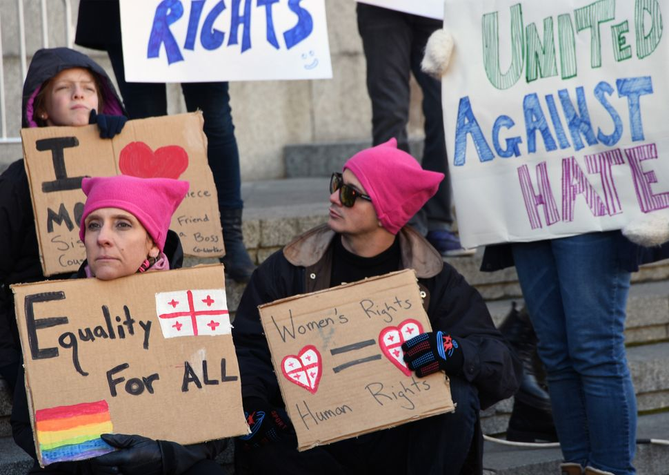 Protesters holding placards take part in the Women's March rally in Tbilisi on January 21, 2017.