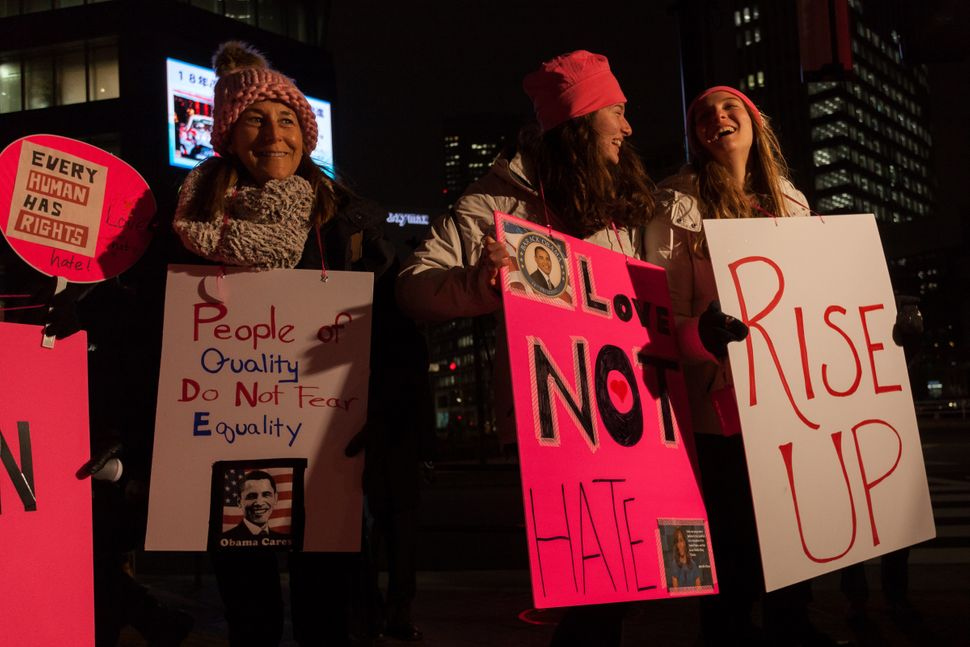 Women wearing pink hats to protest Trump's pussy grabbing comment hold signs before taking part in a protest march by members