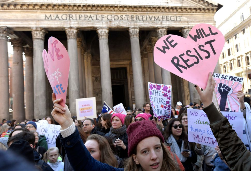 People hold signs during a rally against US newly sworn-in President Donald Trump in Rome on January 21, 2017, a day after Tr