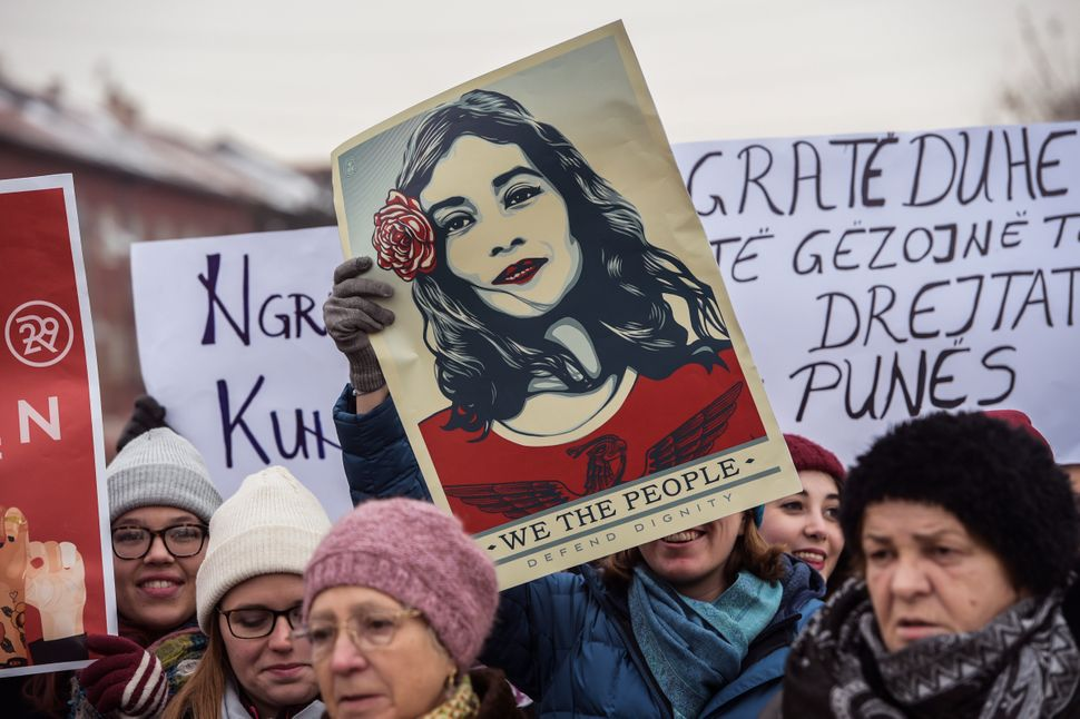 Women hold posters as they take part in a march for women's rights and freedom in solidarity with the march organizedin