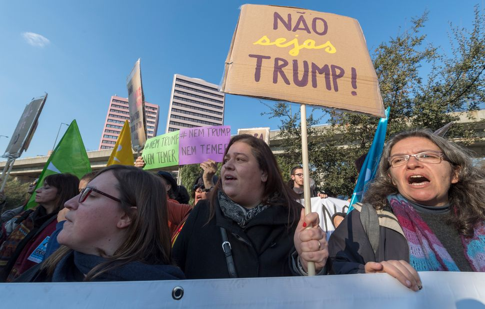 Demonstrators gather to protest against US President Donald Trump in front of the US Embassy on January 21, 2017 in Lisbon, P