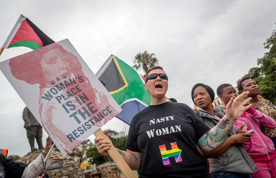 Anti-Trump protesters shout slogans and hold placards during a demonstration, organised by Earthlife Africa, against US newly