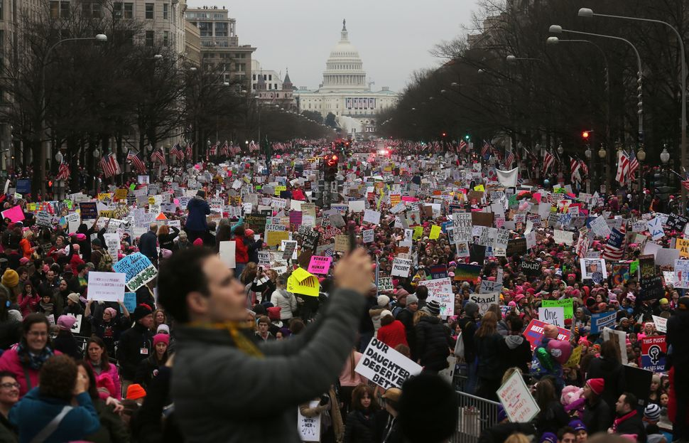 Protesters walk during the Women's March on Washington, with the U.S. Capitol in the background, on January 21, 2017 in