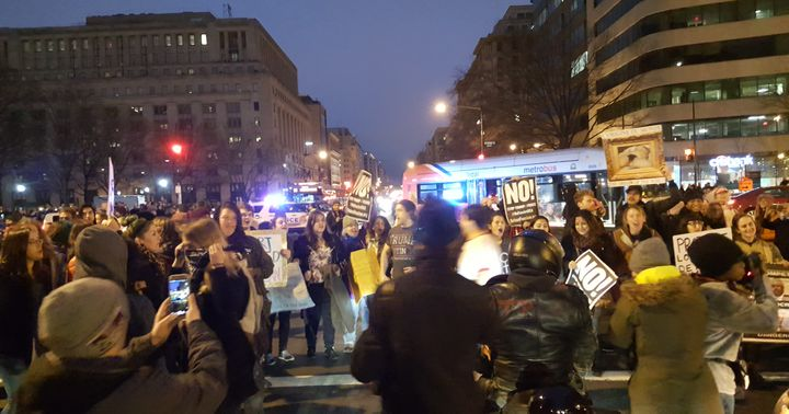 Protestors block buses and cars while shouting grievances with the incoming Trump Administration.