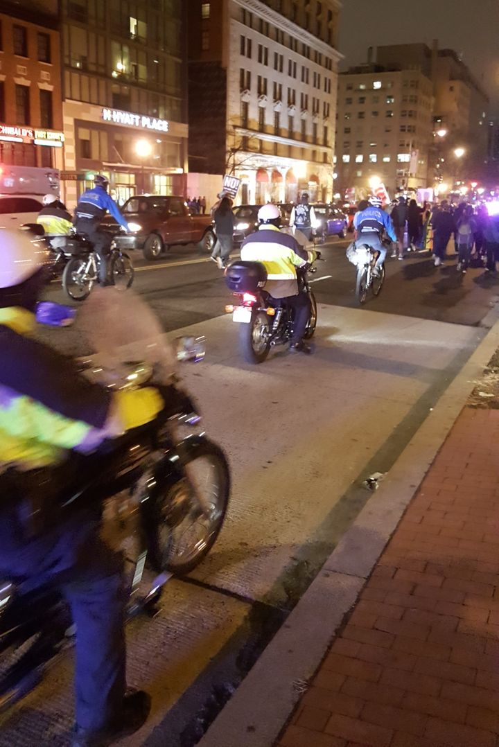 Police provide escort behind marching protesters, following a traffic blocking demonstration.
