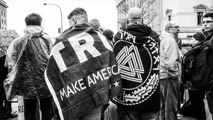 "The Trump supporter on the right is draped in a flag with Aryan runes and a Neo-Nazi symbol called a ""Valknot."""