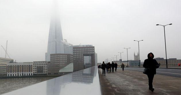 Pedestrians cross London Bridge with the Shard shrouded in fog behind