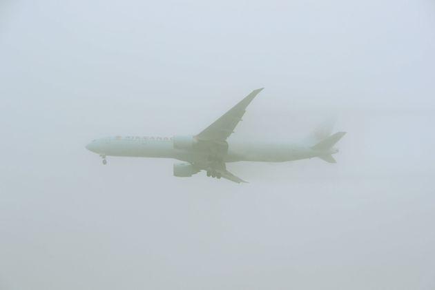 An Air Canada 777-333 comes into land through the fog at Heathrow