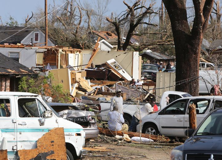 Residents of Magnolia Street in Hattiesburg, Miss., take a break from cleaning up after a tornado hit the area on Saturday, J