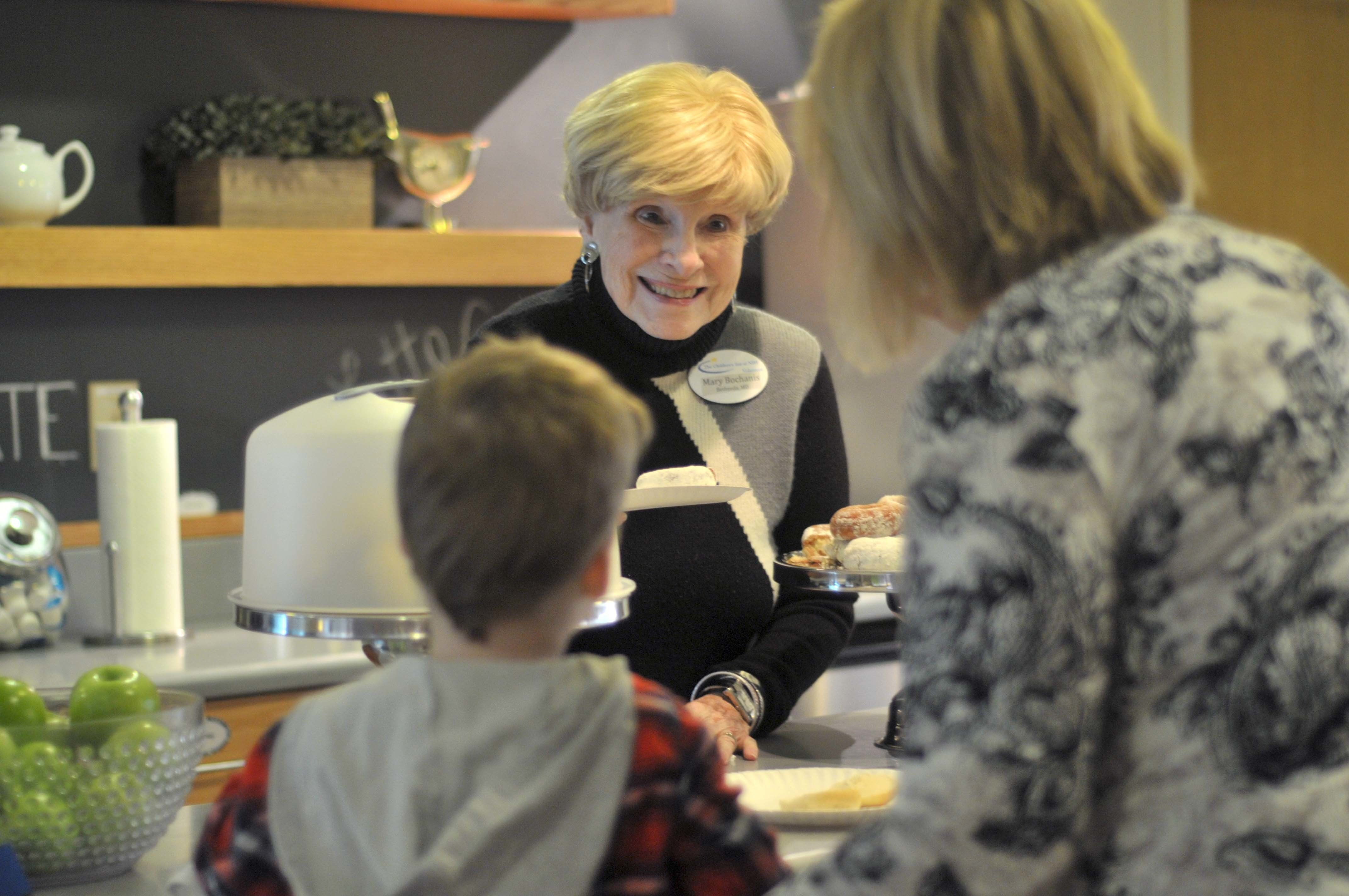 Mary Bochanis who has volunteered at the Childrens Inn at the NIH for over 26 years serves breakfast to a family in the bistro area