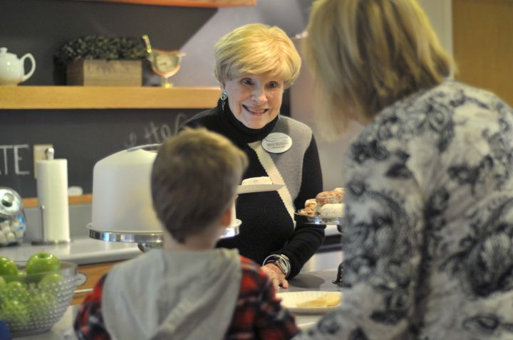 Mary Bochanis, who has volunteered at the Children's Inn at the NIH for over 26 years, serves breakfast to a family.