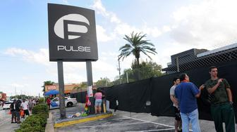 ORLANDO, FLORIDA - JUNE 21:  People leave signs and flowers for the victims of the Pulse Nightclub shooting at the front of the nightclub building on June 21, 2016 in Orlando, Florida. The Orlando community continues to mourn deadly mass shooting at gay club.  (Photo by Gerardo Mora/Getty Images)