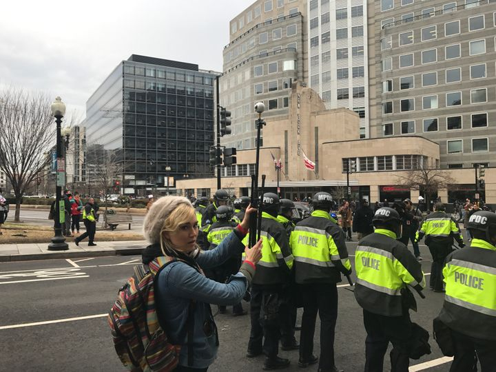 RYOT's Nora Kirkpatrick holds a Samsung Gear360 camera over the heads of riot police on Inauguration Day, Washington D.C.