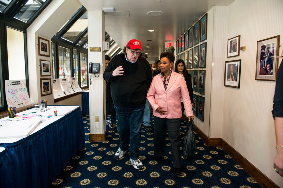 WASHINGTON, DC - JANUARY 20: Michael Moore walks with Congreswoman Barbara Lee during a Huffington Post/Bustle event called ""