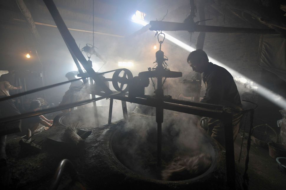 A laborer uses a machine to stir crushed peanuts at a workshop in Rizhao. Dec. 11, 2010.