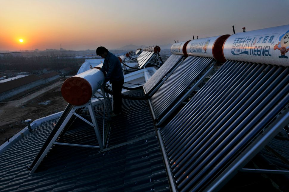 Workers install solar heaters on the roof of a house in Rizhao. Dec. 21, 2009.