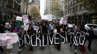 People carry a 'Black Lives Matter' banner during a student walkout protest against US President-elect Donald Trump in Seattle, Washington on November 14, 2016.   / AFP / Jason Redmond        (Photo credit should read JASON REDMOND/AFP/Getty Images)