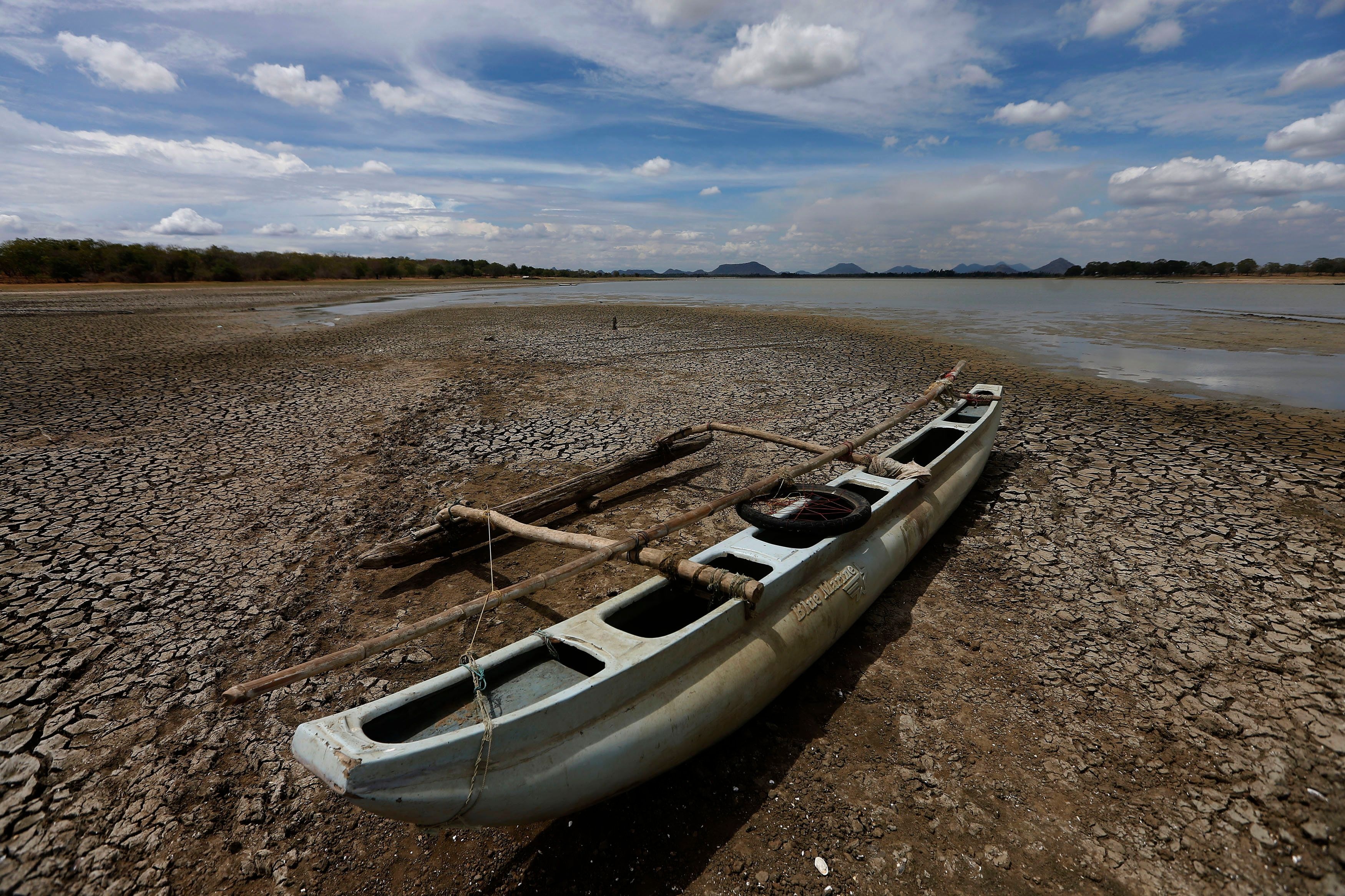 A boat is seen on the dried out bottom of a lagoon in Katharagama August 21, 2014. Sri Lanka's annual inflation rate should not increase sharply due to an extended drought and the government is ready to mitigate any inflationary risks arising from the bad weather, top officials said. REUTERS/Dinuka Liyanawatte (SRI LANKA - Tags: BUSINESS SOCIETY ENVIRONMENT TPX IMAGES OF THE DAY)