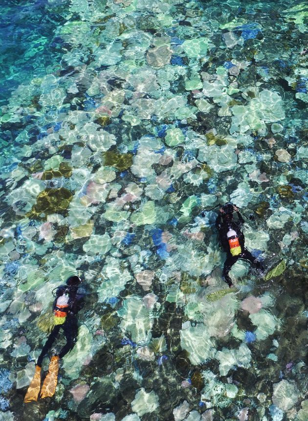 This Sept. 12, 2016 photo, captured from a drone, shows Japan's largest coral reef, Sekiseishoko, between...