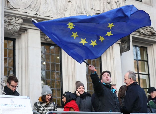 A man waves a flag outside the Supreme Court in London ahead of the