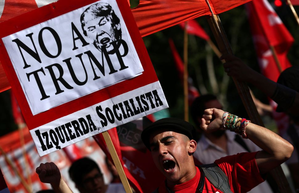 A man shouts slogans as he holds up anti U.S. President Donald Trump signs during a protest outside the U.S. Embassy in Bueno