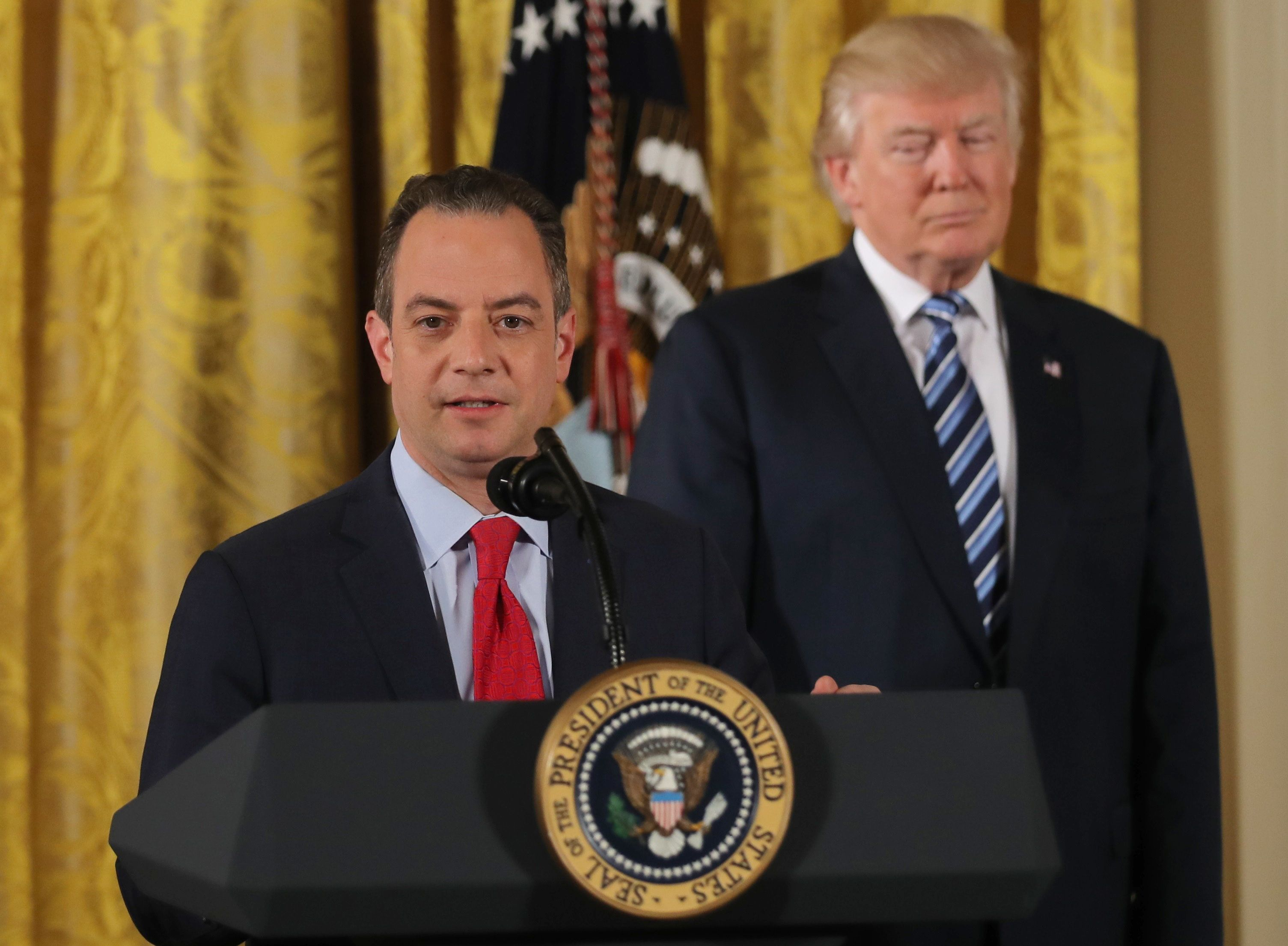 U.S. President Donald Trump stands behinds Chief of Staff Reince Priebus after a swearing-in ceremony for senior staff at the White House in Washington, DC January 22, 2017. REUTERS/Carlos Barria