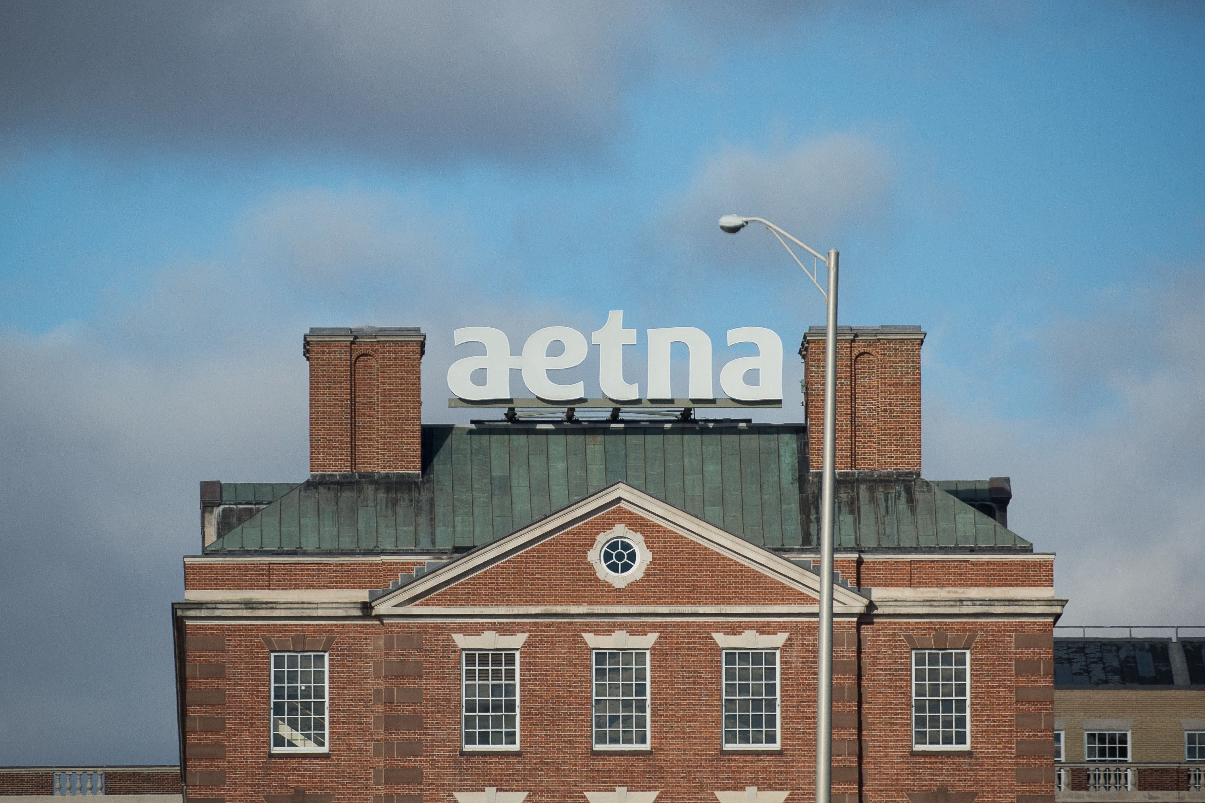 Signage is displayed at Aetna Inc. headquarters in Hartford, Connecticut, U.S., on Tuesday, Nov. 22, 2016. The Justice Department sued to block the union of Aetna Inc. and Humana Inc., saying they would reduce the number of large, national health care insurance providers, leading to increased costs for their clients. Photographer: Michael Nagle/Bloomberg via Getty Images