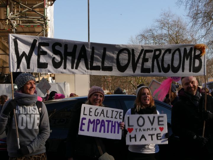"Demonstrators raise a banner saying, ""WE SHALL OVERCOMB,"" at the Women's March on London."