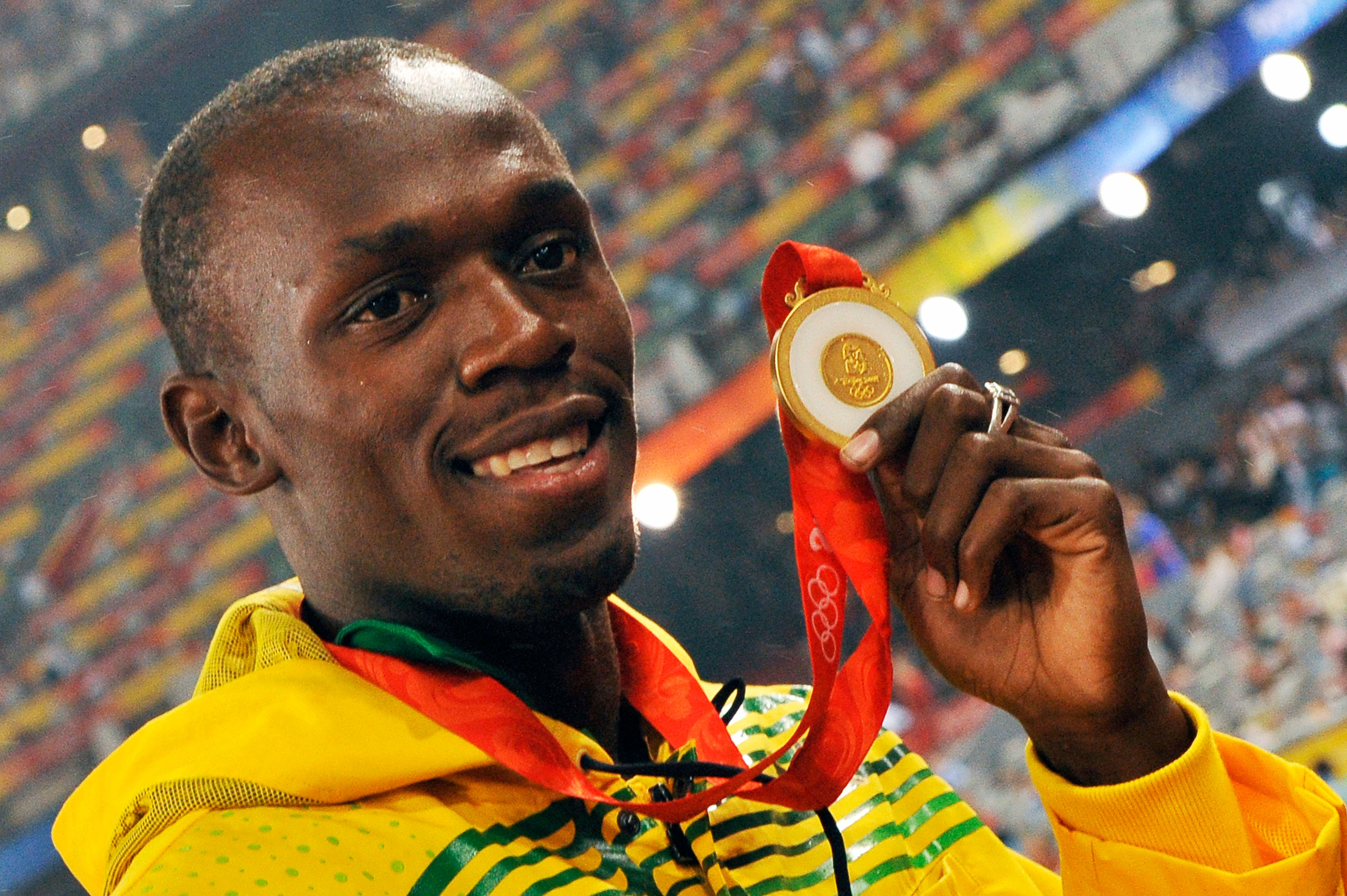Usain Bolt with his gold medal. (Photo by Eddy LEMAISTRE/Corbis via Getty Images)