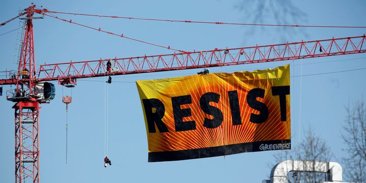 Greenpeace activists urge the public to resist the presidency of Donald Trump.