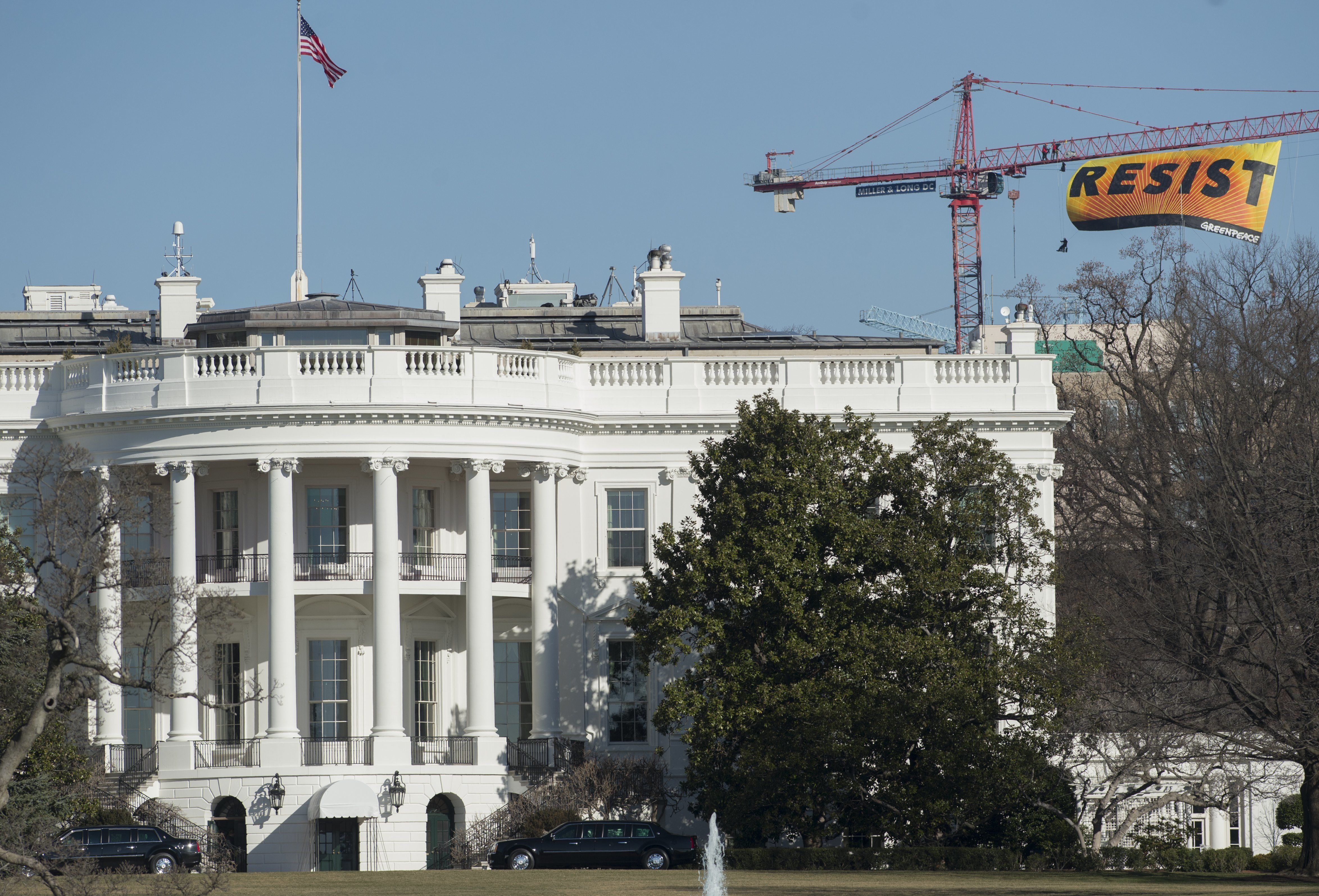 Greenpeace protesters unfold a banner reading 'Resist' from atop a construction crane January 25, 2017 in Washington, DC. The banner, flying high enough to be seen from the White House, is in opposition to the policies of President Donald Trump. / AFP / SAUL LOEB        (Photo credit should read SAUL LOEB/AFP/Getty Images)
