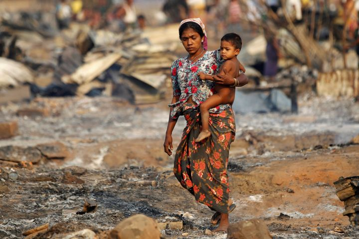 A woman carries a baby past shelters for internally displaced Rohingya Muslims in Myanmar that were destroyed in a fire.