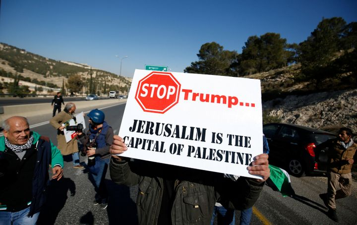 A Palestinian demonstrator holds a placard during a protest against Trump, Jan. 20, 2017.