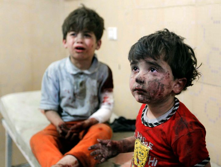 Injured children cry after two barrel bombs were dropped by forces loyal to Syria's president Bashar Assad in Alepp