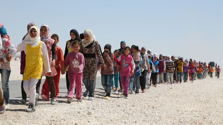 Syrian children march in the refugee camp in Jordan