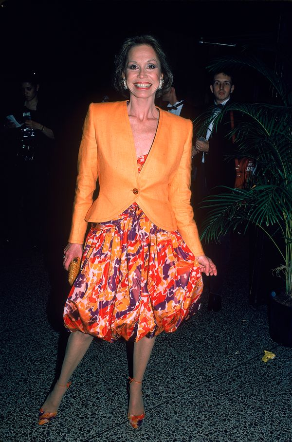 Mary Tyler Moore poses, dressed in a single-button orange jacket and a colorful print dress with a bubble skirt, at an uniden