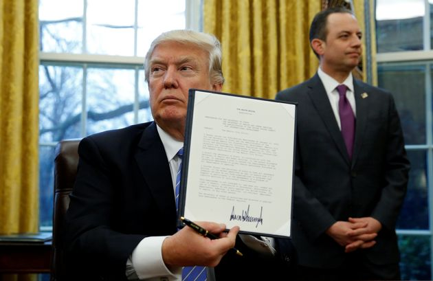 President Donald Trump holds up the executive order on the reinstatement of the Mexico City policy, Jan....