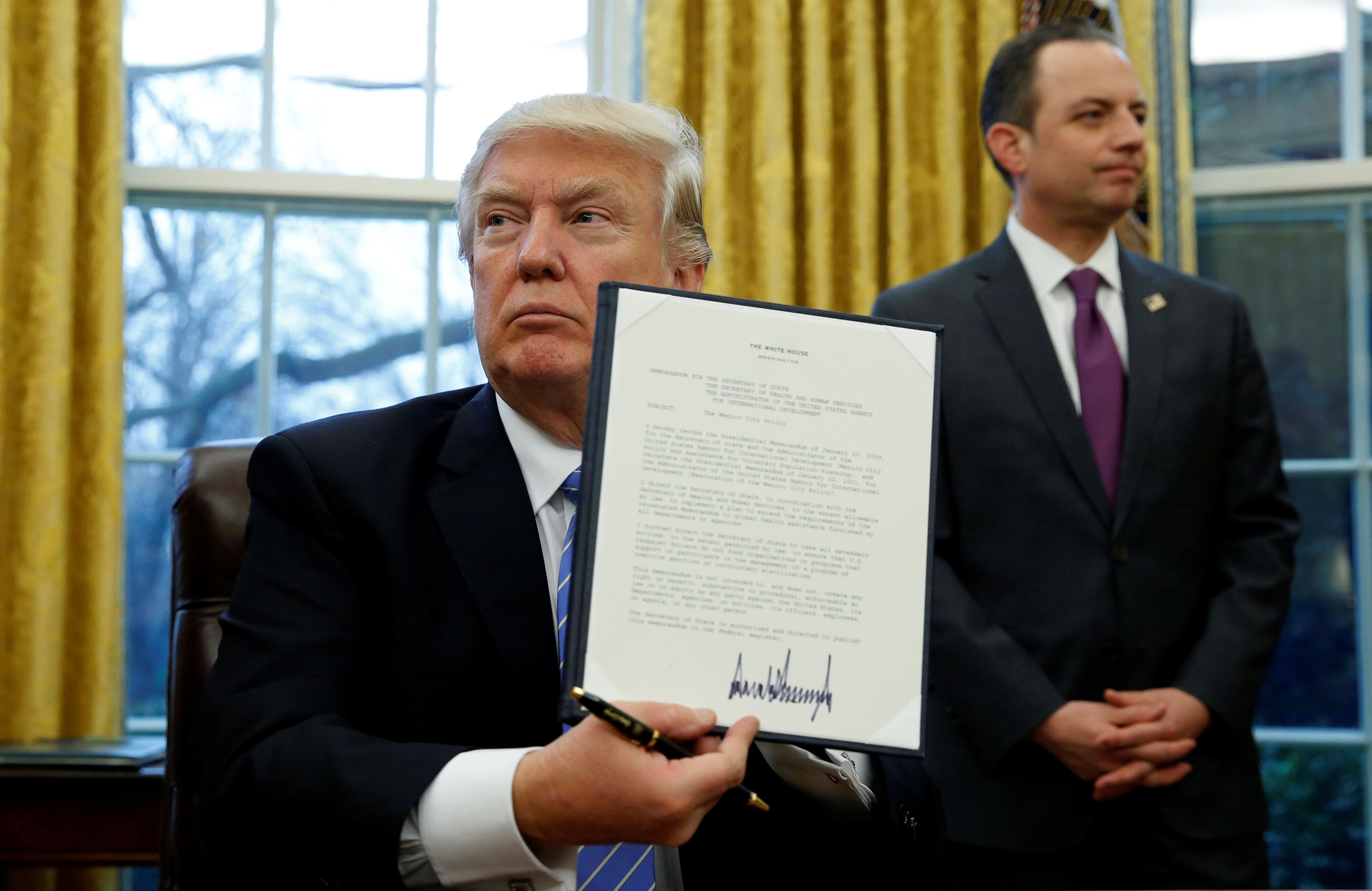 President Donald Trump holds up the executive order on the reinstatement of the Mexico City policy, Jan. 23, 2017. If history