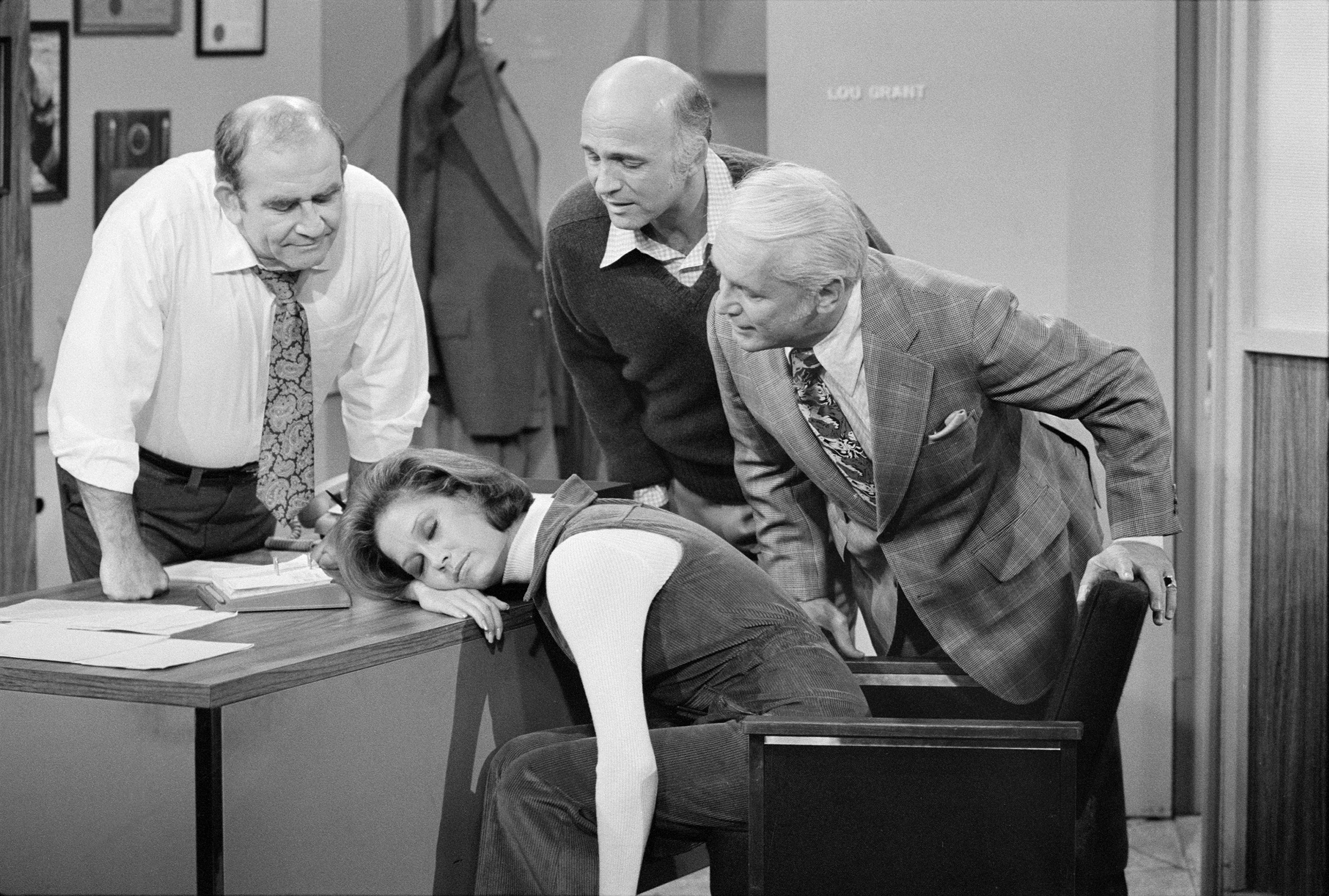 American actress Mary Tyler Moore (as Mary Richards) sleeps on a desk in a scene from the 'Mary's Insomnia' episode of 'The Mary Tyler Moore Show' (also known as 'Mary Tyler Moore'), Los Angeles, California, September 17, 1976. Gathered around her are, fron left, fellow actors Ed Asner (as Lou Grant, on whose desk Mary sleeps), Gavin MacLeod (as Murray Slaughter), and Ted Knight (1923 - 1986) (as Ted Baxter). The episode originally aired on December 4, 1976 (Photo by CBS Photo Archive/Getty Images)