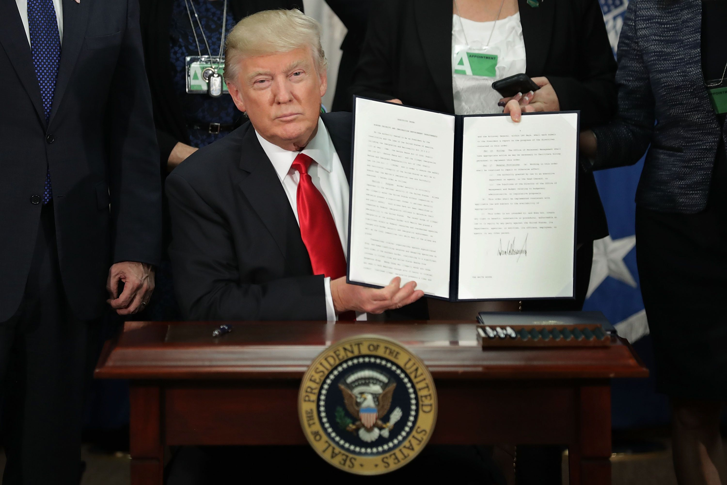 President Donald Trump holds up a signed executive order -- to build a wall on the U.S.-Mexico border -- at the Departme