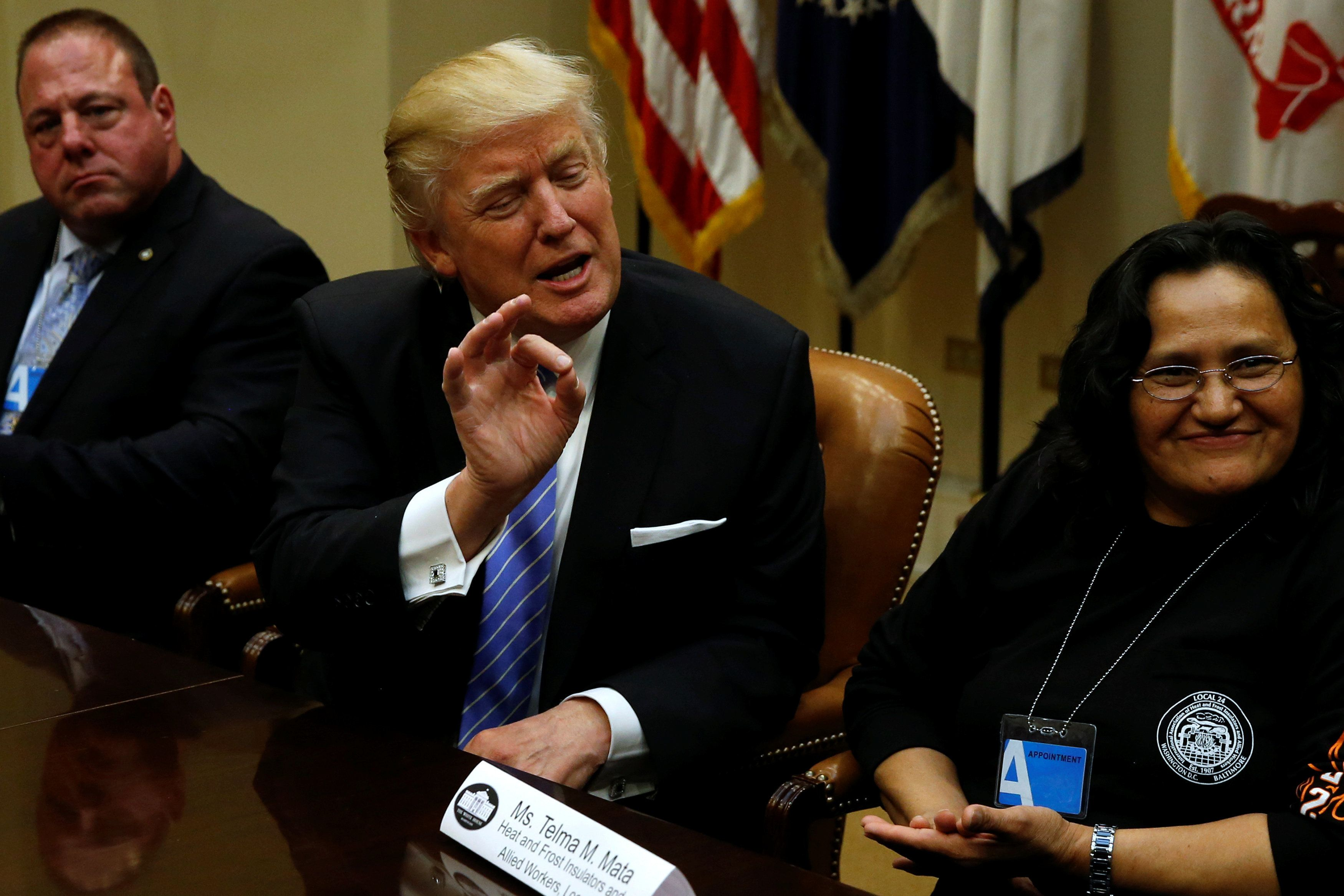U.S. President Donald Trump (C), flanked by Gary Masino (L) of the Sheet Metal Workers Union and Telma Mata (R) of the Heat and Frost Insulators Allied Workers Local 24, holds a roundtable meeting with labor leaders at the White House in Washington, U.S. January 23, 2017.  REUTERS/Jonathan Ernst
