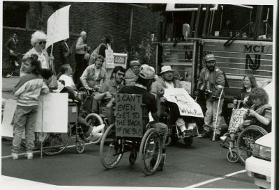 <strong>People with a range of disabilities publicly protesting in front of a bus in the 1970s, before the Americans with Dis