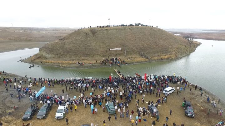Morton County officers occupy Turtle Island, which is sacred to the Sioux Nation.  Protestors gather at its base.