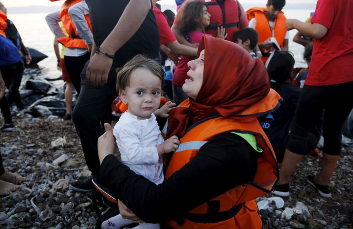 Syrian refugee cries holding her child on the Greek island of Lesbos after crossing a part of the Aegean Sea from Turkey. Sep